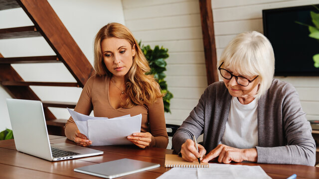 Senior woman with help of her daughter making bills at home