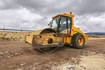 Yellow steamroller performing ground leveling work