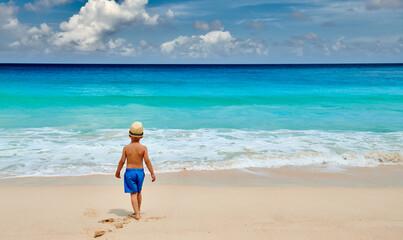 Three year old toddler boy walking on beach