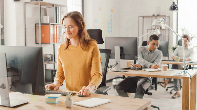 Beautiful and Smart Red Haired Female Specialist Sitting at Her Desk Works on a Desktop Computer. In the Background Modern Bright Office with Diverse Group of Professionals Working for Growing Startup