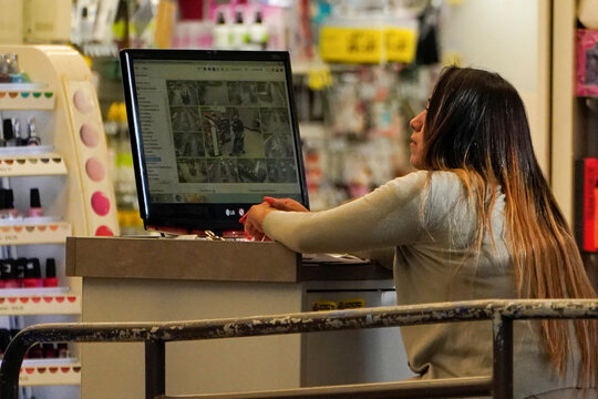 A Rite Aid store worker looks over security camera footage from facial recognition cameras in one of the company's stores in downtown Los Angeles