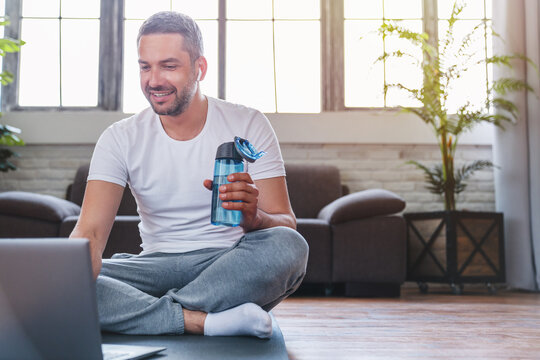 Middle aged man using laptop and drinking water while having break during workout at home