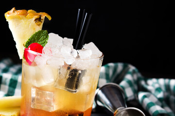 Cold mai tai cocktail with pineapple and cherry in glass on wooden table