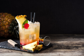 Cold mai tai cocktail with pineapple and cherry in glass on wooden table. Copy space