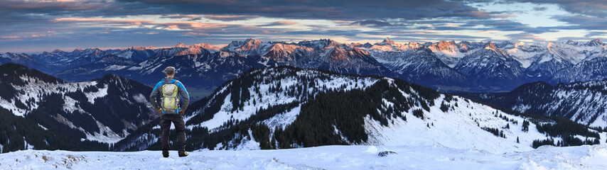 Wall Mural - Hiker Man with Backpack standing on snow winter mountain with view to amazing sunset alpenglow panorama of mountain ranges and dramatic sky. View from Riedbergerhorn to Allgau Alps. Bavaria, Germany.