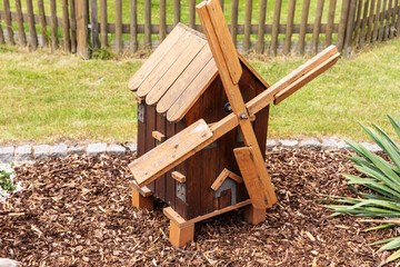Small wooden decorative brown mill stands in the garden