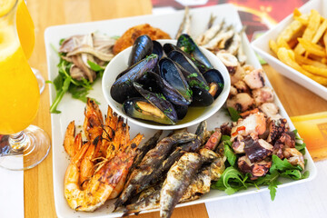 A sea food plate with grilled, fried and marinated fish, shrimps, squids and cooked mussels with wine and garlic