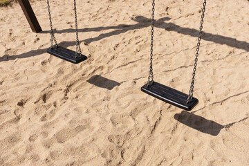 Empty swing for the children on the playground on the sand on the park