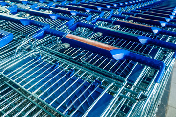 Many shopping carts parked in front of a supermarket.