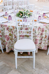 Crystal cutlery and flowery tablecloth on a tastefully decorated wedding table and white chair.
