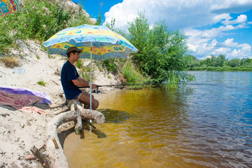 The young guy catches a fish with a fishing rod, sitting on the Desna river bank under an umbrella from the sun.