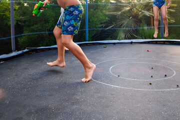 Unrecognizable children jumping on a trampoline with swimming trunks and enjoying their friends in a group.