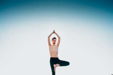 Young man in a Namaste greeting position while freeing his mind from worries in tree pose.
