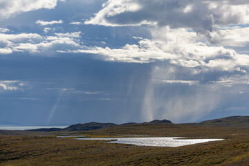 Thunderclouds lit with sunshine with the rain over Barents sea, Finnmark, Norway