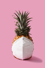 Pineapple with protective face mask on pink background