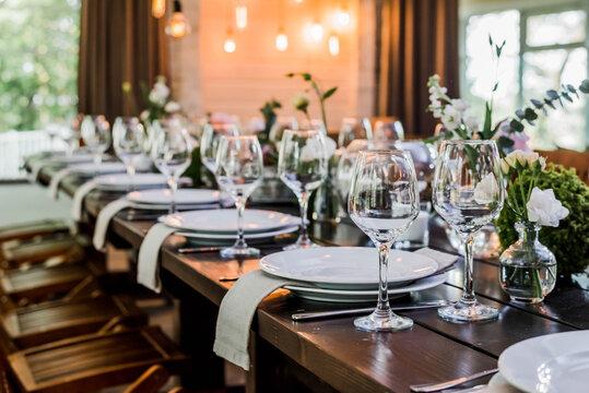 Wedding reception table with Edison bulbs and decor of greenery. Decoe. Wedding table setting