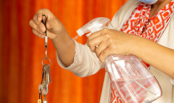 woman sanitizing objects with alcohol spray and disinfectant