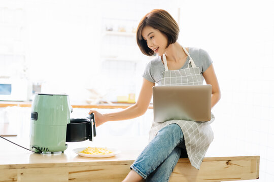 Portrait of beautiful Asian woman working on laptop while cooking with Air Fryers in kitchen during coronavirus pandemic.Remote work at home during self-isolation quarantine.New normal concept.