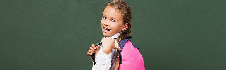 horizontal concept of happy schoolgirl pointing with thumb at backpack near chalkboard