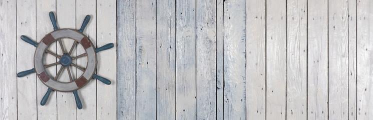 wooden steering wheel on white wooden background