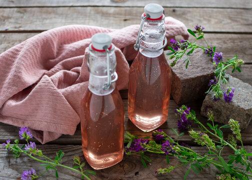 Frischer Lavendelsirup in dekorativen Einweckflaschen abgefüllt auf Holz