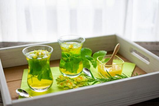 zwei frisch aufgebrühte Tees aus Zitronenmelisse und Leinkraut in türkischen Teegläsern auf einem Tablett.