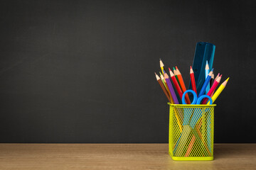 Green pencil holder with stationary supplies against blank black chalkboard, back to school concept