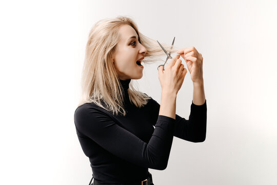 Woman cutting off her own hair on gray background.