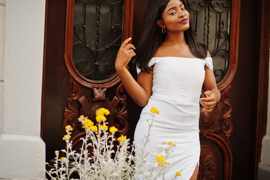 African american woman in white dress posed outdoor.