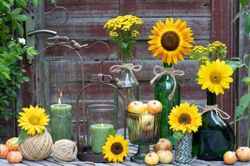 Gartendekoration mit Sonnenblumen in Glasflaschen, Äpfeln und Laternen