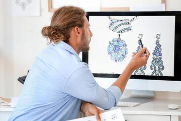 Male jewelry designer working in office