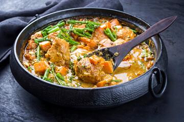 Modern Style afrikanische Krokodil Bäckchen in Curry mit Süßkartoffel, Brokkoli und Erdnüsse als close-up in einem modern Design Topf