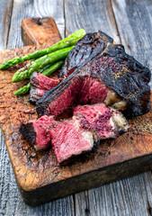 Gegrilltes dry aged Wagyu Bistecca alla Fiorentina Steak vom Rind mit großen Filet Stück mit grünen Spargel und Rotwein Salz angeboten als close-up auf einem alten rustikalen Holz Board