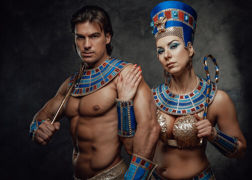Woman in traditional egyptian costume holds male sholder and the sign of power and royalty.