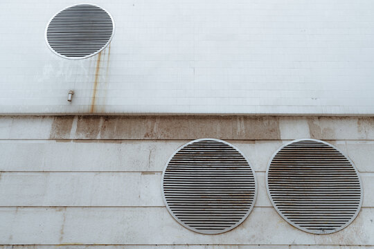 View of a dull futuristic wall in cyberpunk style with three huge round ventilation shafts covered with grills, rusty streaks on the tiled part above