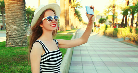 Happy smiling woman taking selfie picture by smartphone over palm tree background