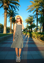 Attractive woman wearing a striped dress and summer straw hat outdoors over palm trees background