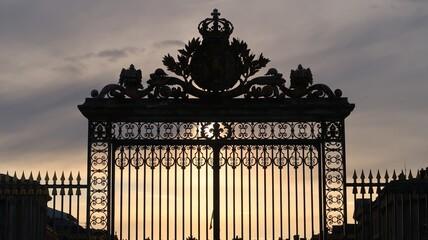 Grille royale du château de Versailles, portail d'entrée en fer forgé, à contre-jour au soleil couchant (France)