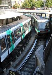 Vue sur des rails et deux métros se croisant dans une station de métro RATP à Paris – 18 juillet 2020 (France)