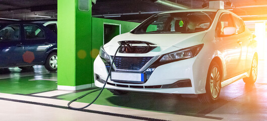 Eco auto. Electric car charge battery on eco energy charger station. Hybrid vehicle - green...