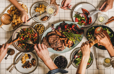 Summer barbeque party. Flat-lay of table with grilled meat, vegetables, salads, roasted potato and peoples hands over white tablecloth, top view. Family gathering, feasting, comfort food concept