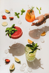 Popular bar summer ice alcoholic cocktails. Gin-tonic, Aperol Spritz and strawberry basil Margarita in glasses and womans hand reaching for glass over plain white background with fruit pieces