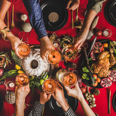 Friends celebrating Christmas. Flat-lay of people clinking glasses with rose wine over festive table with red cloth with roasted chicken, bundt cake, fruit, decorations, top view, square crop