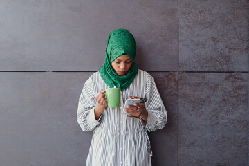 african muslim businesswoman with green hijab using mobile phone