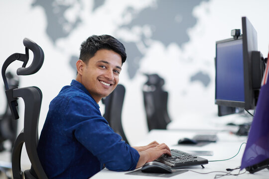 casual indian business man working on desktop computer