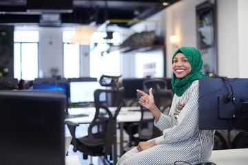 portrait of african muslim business woman sitting on desk