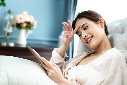 Beautiful charming Asian woman sitting on white sofa and using digital tablet connecting to social networking at living room in the morning. Happiness relaxation at home