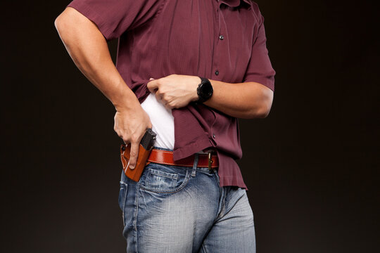 Man lifting up his shirt about to draw his concealed carry pistol from his holster.