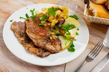 Appetizing pork steaks with side dish of boiled potatoes with fried onion and fresh greens