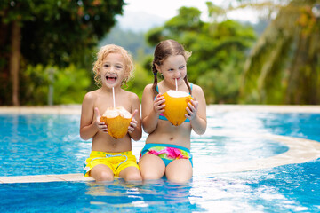 Child with coconut drink. Kids in swimming pool.